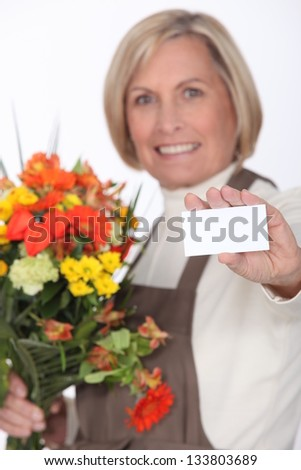 Middle-aged female florist holding out business card - stock photo