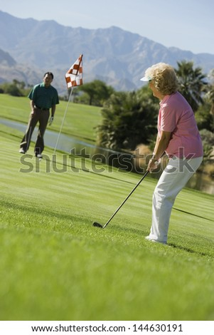 Middle aged female golfer with friend on golf course