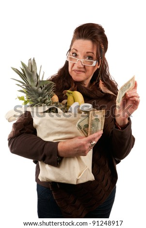 Middle aged female shopper smiling with a handful of cash acting proud of how much money she has saved on her grocery shopping bill. - stock photo