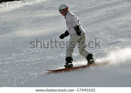 Middle aged female snowboarder wearing helmet and snow goggles in powder snow on steep hill - shot in Livigno, Italian Alps - stock photo