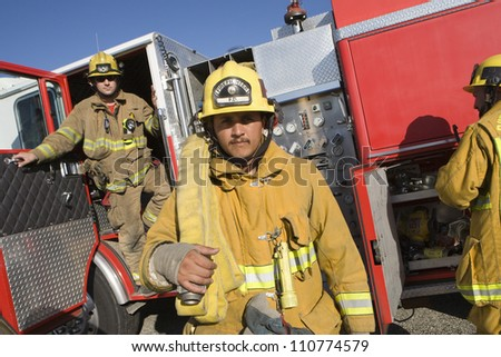 Middle aged fire worker carrying fire hose - stock photo