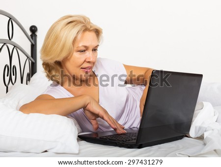 Middle-aged girl with laptop laying in her bed at home