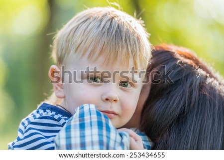 middle-aged grandmother holds little grandson in her arms family - stock photo