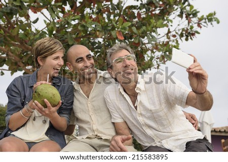 Middle aged group of friends taking a selfie with phone - stock photo