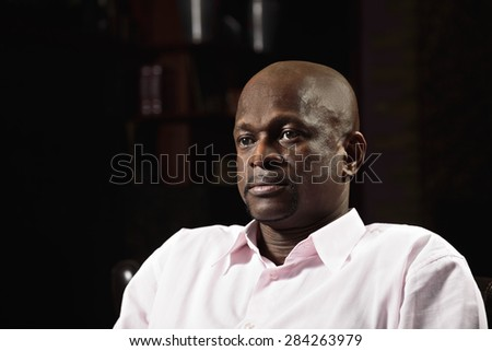 Middle-aged guy in pink shirt looking sideways - stock photo
