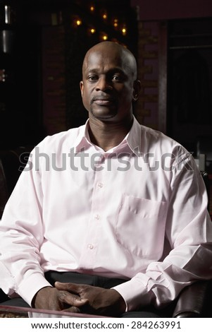 Middle-aged guy in pink shirt sitting at the table - stock photo