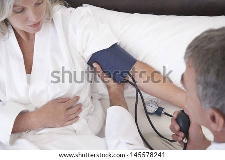 Middle aged gynecologist taking blood pressure of female patient at home - stock photo