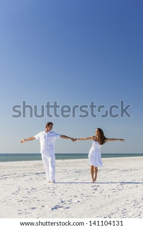 Middle aged happy man and woman romantic couple in white clothes dancing on a deserted tropical beach with bright clear blue sky - stock photo