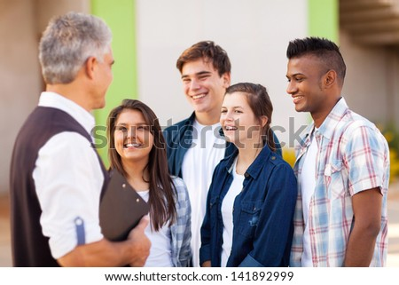 middle aged high school teacher talking to students during break - stock photo