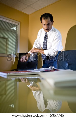 Middle-aged Hispanic businessman working in office rolling up sleeves looking down at paperwork - stock photo