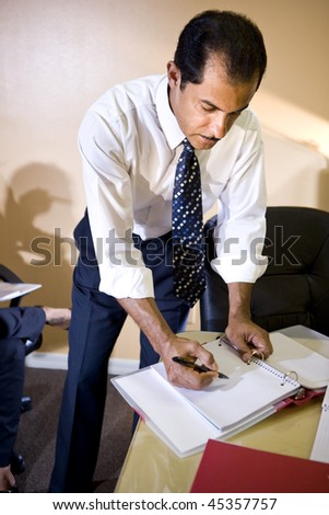 Middle-aged Hispanic businessman working in office writing notes in binder - stock photo