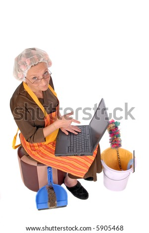 Middle aged housewife with curlers in hair planning household on laptop. House cleaning utensils on the side. - stock photo