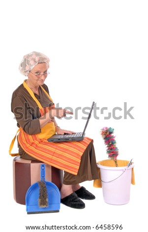 Middle aged housewife with curlers in hair planning household on laptop. House cleaning utensils on the side.