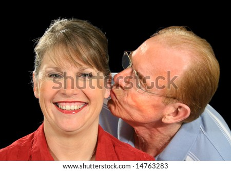 Middle aged husband gives his wife a peck on the ear.