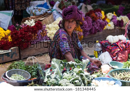 Middle-aged indigenous woman sells vegetables and flowers at traditional weekly market in Chichicastenango (Chichi), Guatemala. - stock photo