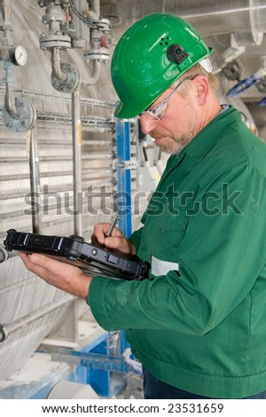 Middle aged industrial worker with notebook - stock photo