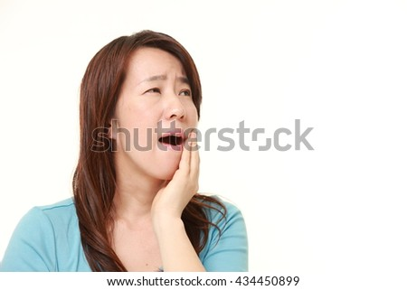 middle aged Japanese woman suffers from toothache - stock photo