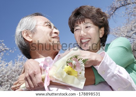 middle aged Japanese woman who hugs a husband