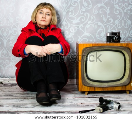 Middle aged lady sitting on old floor next to retro tv and photo camera - stock photo