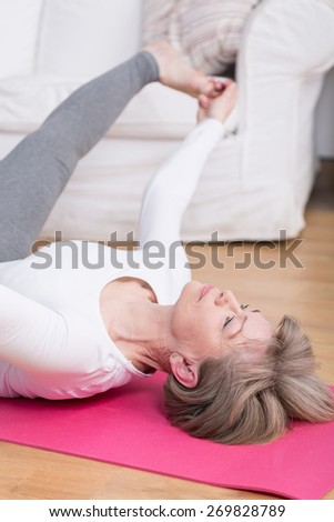 Middle aged lady stretching on the floor mat