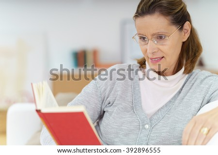 Middle-aged lady wearing reading glasses relaxing at home on the sofa with a book, close up upper body view