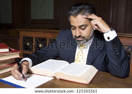 Middle aged lawyer referring law book to study the case in the courtroom - stock photo
