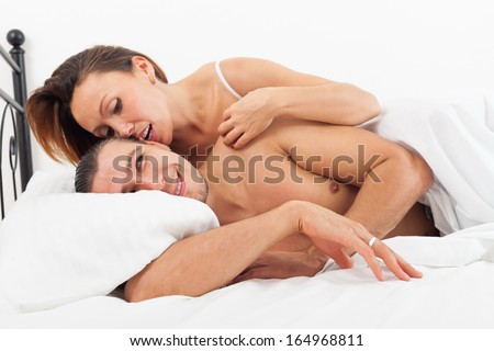 Middle-aged lovers kissing and playing in bed at home - stock photo