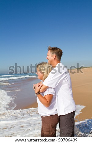 middle-aged loving couple hugging on beach - stock photo