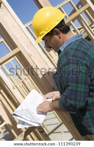 Middle aged male architect reading blueprint at construction site - stock photo