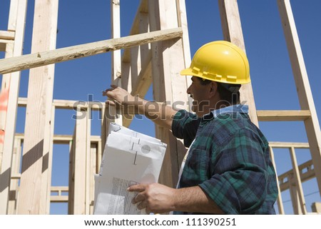 Middle aged male architect reading blueprint at construction site