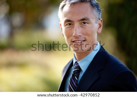 Middle aged male businessman in suit and tie standing outside. Horizontally framed shot.