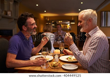 Middle aged male couple eating evening meal in a restaurant - stock photo