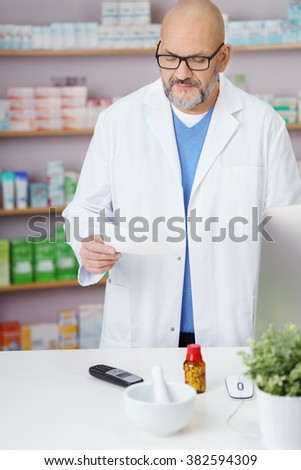 Middle-aged male pharmacist checking a prescription at the pharmacy as he stands behind the counter in a white lab coat - stock photo