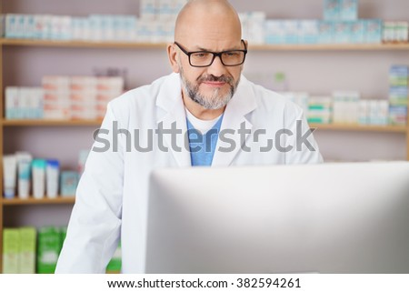 Middle-aged male pharmacist checking information on his computer with a serious expression as he stands in front of shelves of merchandise - stock photo