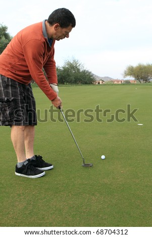 middle-aged man about to make a golf putt - stock photo