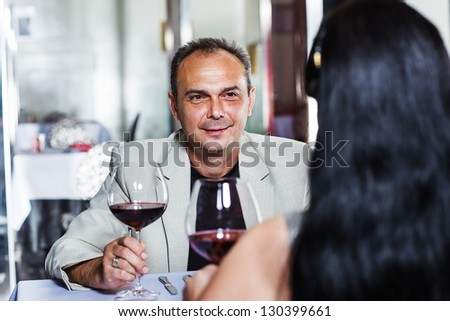Middle aged man and his wife having romantic dinner in a restaurant - stock photo