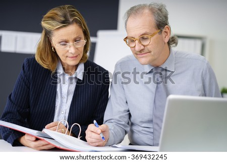 middle-aged man and woman in the office working together on papers, businessman signing a document - stock photo