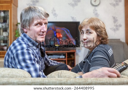 Middle-aged man and woman sitting in front of TV turning back on couch - stock photo