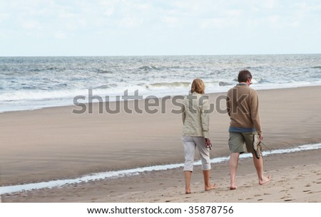 Middle aged man and woman taking a walk on the beach. - stock photo