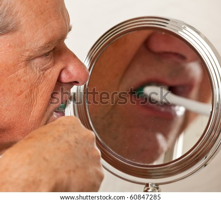 Middle aged man cleaning teeth in front of shaving mirror with electric toothbrush - stock photo