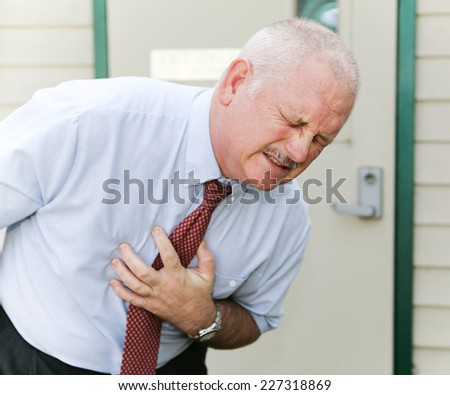 Middle-aged man doubled over with his hand on his abdomen.  Could be symptoms of heart attack, angina, nausea, ebola, or other illness.   - stock photo