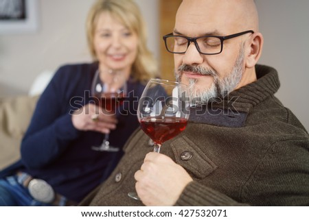 Middle-aged man enjoying a glass of red wine sniffing the bouquet with his eyes closed in bliss watched by his wife alongside him - stock photo