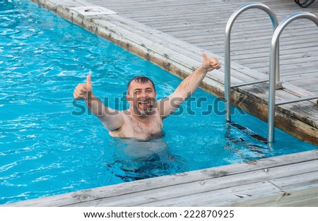 Middle-aged man enjoying summertime in a swimming pool