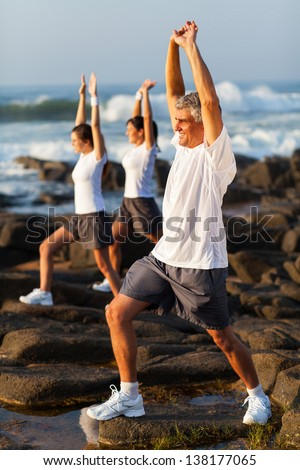 middle aged man exercising with his family at the beach - stock photo