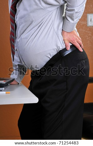 Middle aged man experiencing back pain upon standing.  Overweight mid section creates the pain because of the size of belly and is at risk for heart attacks and stroke. Unlit cigarette seen on desk.