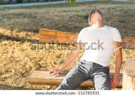 Middle-aged man experiencing euphoria after using psychoactive drugs sitting on a bench in the park - stock photo