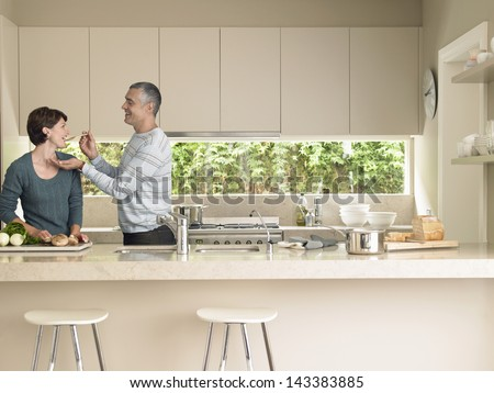 Middle aged man feeding wife at kitchen counter - stock photo