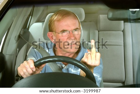 Middle aged man gives rude sign in road rage incident. - stock photo