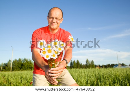 Middle-aged man giving flowers - stock photo