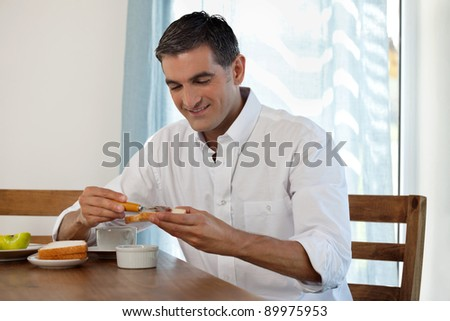 Middle aged man having breakfast at home - stock photo